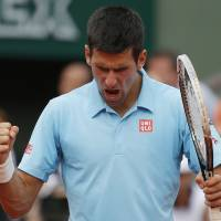Photo - Serbia's Novak Djokovic reacts after a winning point as he plays Spain's Rafael Nadal during their final match of  the French Open tennis tournament at the Roland Garros stadium, in Paris, France, Sunday, June 8, 2014. (AP Photo/Michel Euler)