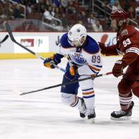 Photo - Edmonton Oilers' Sam Gagner (89) skates in front of Phoenix Coyotes' Derek Morris (53) during the first period of an NHL hockey game, Friday, April 4, 2014, in Glendale, Ariz. (AP Photo/Ross D. Franklin)