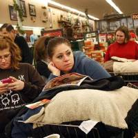Photo - Christy Embry, left, and Crystal Coleman wait in a long checkout line Nov. 24 during the Black Friday sale at Bass Pro Shops, in Memphis, Tenn.