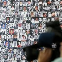 Photo - A wall of photographs of journalists killed while reporting the news lines a wall during the rededication of the Journalists Memorial at the Newseum in Washington, Monday, June 9, 2014. The memorial, which recognizes journalists killed while covering the news, added 10 names of journalists who were killed in 2013. (AP Photo/Charles Dharapak)