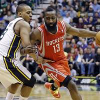 Photo - Houston Rockets' James Harden (13) drives around Utah Jazz's Randy Foye (8) during the second quarter of an NBA basketball game, Monday, Jan. 28, 2013, in Salt Lake City. (AP Photo/Rick Bowmer)