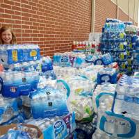 Photo -  9-year-old Emma Kitchel can hardly see over the donations of water outside her grandmother's church.