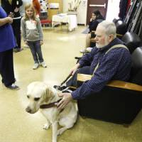 Photo - Ralph Haney, president of the Oklahoma Guide Dogs Alumni Association, talks about his guide dog, Tallis, with Dacia Sims, 9, at Martin Park Nature Center in Oklahoma City. Photos by Paul Hellstern, The Oklahoman