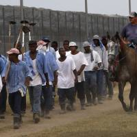 Photo - FILE - In this Aug. 18, 2011 file photo, a prison guard on horseback watches inmates return from a farm work detail at the Louisiana State Penitentiary in Angola, La. As summer approaches, corrections officials throughout the country must deal with prisoners' potentially fatal exposure to extreme heat. Advocates say rising temperatures are a threat to an increasingly mentally ill and aging prisoner population. Lawsuits over heat conditions in jails and prisons have been filed in Arizona, Wisconsin, Illinois, Louisiana, Georgia and Delaware. (AP Photo/Gerald Herbert, File)