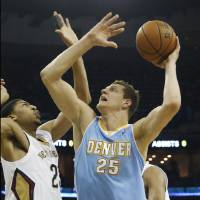 Photo - Denver Nuggets center Timofey Mozgov (25) shoots over New Orleans Pelicans power forward Anthony Davis (23) in the first half of an NBA basketball game in New Orleans, Sunday, March 9, 2014. (AP Photo/Bill Haber)