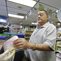 Photo - Remberto Gonzalez purchases Powerball lottery tickets at a local store in Hialeah, Fla., Tuesday, Aug. 6, 2013. On Tuesday, the Powerball jackpot reached $425 million for Wednesday's drawing. (AP Photo/Alan Diaz)