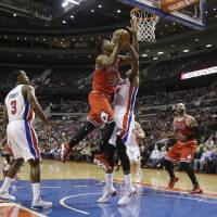 Photo - Chicago Bulls guard Jimmy Butler (21) shoots over the defense of Detroit Pistons forward Greg Monroe (10) during the first half of an NBA basketball game in Auburn Hills, Mich., Wednesday, March 5, 2014. (AP Photo/Carlos Osorio)