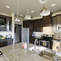 Photo - Hanging lights lend a professional air to the kitchen at 8400 NW 141 Circle, built by TimberCraft Homes for the Parade of Homes Oct. 19-27.  PAUL B. SOUTHERLAND - The Oklahoman