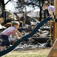 Photo - Sisters Cheyann, 5, and Sara Ford, 3, play on a wooden swing set that escaped the flames. The girls were visiting their grandmother who lives next door to this burned house. The grandmother's house, 1004 Pacific, received minor damage. FEMA toured several neighborhoods on Tuesday, April 14, 2009. Photo by JIM BECKEL