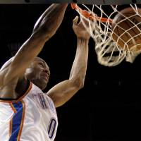 Photo - Oklahoma City Thunder's Russell Westbrook dunks unopposed against the Phoenix Suns in the first quarter of a preseason NBA basketball game in Oklahoma City, Monday, Oct. 12, 2009. (AP Photo/Sue Ogrocki) ORG XMIT: OKSO106
