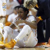 Photo - Tennessee guard Ariel Massengale (5) is assisted by head coach Holly Warlick after being injured in the first half of an NCAA college basketball game Thursday, Jan. 23, 2014, in Knoxville, Tenn. Massengale didn't return to the game after getting hit in the face while making a steal late in the first half. No. 11 Tennessee defeated Florida 89-69. (AP Photo/Wade Payne)