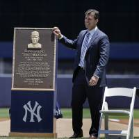 Photo - Former New York Yankees first baseman Tino Martinez stands next to a plaque dedicated to his time with the Yankees before a baseball game against the Baltimore Orioles, Saturday, June 21, 2014, in New York. The plaque will be displayed at the stadium's Monument Park. (AP Photo/Julie Jacobson)