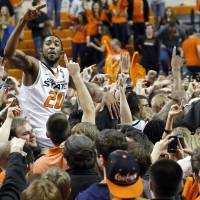 Photo - Oklahoma State's Michael Cobbins (20) celebrates with fans during the Bedlam men's college basketball game between the Oklahoma State University Cowboys and the University of Oklahoma Sooners at Gallagher-Iba Arena in Stillwater, Okla., Saturday, Feb. 16, 2013. Photo by Sarah Phipps, The Oklahoman