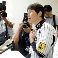 Photo -   The Japan Professional Baseball Players Association Chairman Takahiro Arai speaks during a news conference in Nishinomiya, Japan, Tuesday, Sept. 4, 2012. The association agreed to take part in the 2013 World Baseball Classic Tuesday, backing off from a threat to boycott the event over the way tournament revenue is shared. (AP Photo/Kyodo News) JAPAN OUT, MANDATORY CREDIT, NO LICENSING IN CHINA, HONG KONG, JAPAN, SOUTH KOREA AND FRANCE