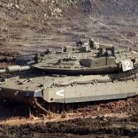 Photo -   An Israeli tank in a firing position in the Israeli-controlled Golan Heights overlooking the Syrian village of Bariqa, Monday, Nov. 12, 2012. The Israeli military says