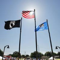 Photo - The POW-MIA, American and Oklahoma flags were raised during the dedication of the Midwest City veterans memorial on Friday. Photo by Paul B. Southerland, The Oklahoman  PAUL B. SOUTHERLAND - PAUL B. SOUTHERLAND