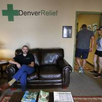 Photo - In this Aug. 25, 2014 photo, Kayvan Khalatbari, left, sits on the couch in the lobby of his medical and recreational marijuana store Denver Relief, as his employee Allison Woods escorts a customer into the shop, in Denver. Khalatbari also runs Denver Relief Consulting, which assists current and would-be marijuana-related businesses around the country, as well as owning a chain of pizza restaurants in Denver. (AP Photo/Brennan Linsley)