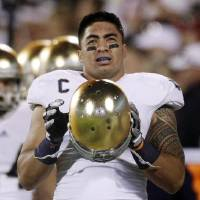 Photo - FILE - In this Oct. 27, 2012, file photo, Notre Dame linebacker Manti Te'o stands on the sidelines during an NCAA college football game against Oklahoma in Norman, Okla. Notre Dame issued a release Wednesday, Jan. 16, 2013, saying a story about Te'o's girlfriend dying, which he said inspired him to play better as he helped the Fighting Irish get to the BCS title game, turned out to be a hoax apparently perpetrated against the linebacker. (AP Photo/Sue Ogrocki, File)
