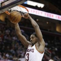 Photo - Cleveland Cavaliers' Tristan Thompson (13) dunks in front of Toronto Raptors' Jonas Valanciunas (17) during the second quarter of an NBA basketball game Wednesday, Feb. 27, 2013, in Cleveland. (AP Photo/Tony Dejak)