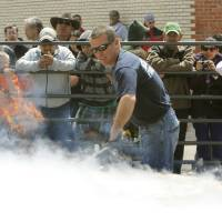 Photo - El Reno Fire Chief Kent Lagaly pats down a 750-pound burger during the  Burger Day Festival.  Photo by Paul Hellstern, The Oklahoman  PAUL HELLSTERN - Oklahoman