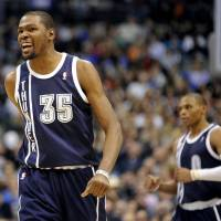 Photo - Oklahoma City Thunder forward Kevin Durant (35) and guard Russell Westbrook celebrate after a basket in the second quarter during an NBA basketball game against the Dallas Mavericks, Friday, Jan. 18, 2013, in Dallas. (AP Photo/Matt Strasen)