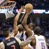 Photo - Oklahoma City's Serge Ibaka and Russell Westbrrok fight over a rebound  during the second half of their NBA basketball game against Toronto at the OKC Arena in downtown Oklahoma City on Sunday, March 20, 2011. The Raptors beat the Thunder 95-93. Photo by John Clanton, The Oklahoman