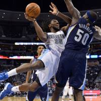 Photo - Denver Nuggets forward Kenneth Faried (35) goes up for a shot against Memphis Grizzlies forward Zach Randolph (50) during the third quarter of an NBA basketball game on Monday, March 31, 2014, in Denver. (AP Photo/Jack Dempsey)