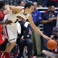 Photo - Arizona's Aaron Gordon (11) struggles with Utah's Delon Wright, left, as he drives toward the basket in the second half of an NCAA college basketball game on Sunday, Jan. 26, 2014, in Tucson, Ariz. (AP Photo/John Miller)