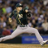 Photo - Oakland Athletics starting pitcher Sonny Gray throws against the Seattle Mariners in the sixth inning of a baseball game, Saturday, April 12, 2014, in Seattle. (AP Photo/Ted S. Warren)