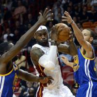 Photo - Miami Heat's LeBron James, center, is defended by Golden State Warriors' Draymond Green (23) and Stephen Curry (30) during an NBA basketball game on Wednesday, Dec. 12, 2012, in Miami. (AP Photo/Rhona Wise)