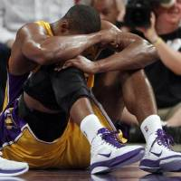 Photo - Los Angeles Lakers' Andrew Bynum holds his knee on the floor after being hurt during the first half of a NBA basketball game against the San Antonio Spurs in Los Angeles, Tuesday, April 12, 2011. Bynum hyperextended his right knee. (AP Photo/Chris Carlson)  Chris Carlson