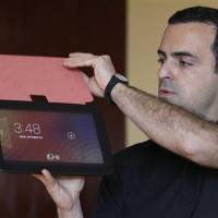 Photo - Hugo Barra, Android at Google Director of Product Management, holds up the Nexus 10 tablet at a Google announcement in San Francisco, Monday, Oct. 29, 2012. The tablet computer is without a doubt the gift of the year. just like it was last year. But if you resisted the urge in 2011, now is the time to give in. This season's tablets are better all around. Intense competition has kept prices very low, making tablets incredible values compared to smartphones and PCs  (AP Photo/Jeff Chiu)