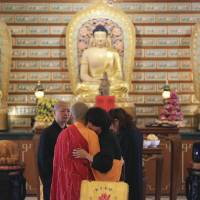 Photo - A Chinese relative of passengers on board the missing Malaysia Airlines Flight MH370 is comforted by a monk as she breaks into tears following prayers at a Buddhist temple in Petaling Jaya, Malaysia, Monday March 31, 2014. Relatives from China are in the country to seek answers of what happened to their loved one on board flight MH370. (AP Photo/Aaron Favila)