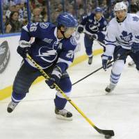 Photo - Tampa Bay Lightning right wing Martin St. Louis, left, controls the puck against Toronto Maple Leafs defenseman Mike Kostka during the second period of an NHL hockey game Tuesday, Feb. 19, 2013, in Tampa, Fla. (AP Photo/Brian Blanco)