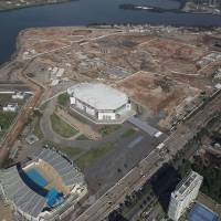 Photo - This June 27, 2014 aerial view photo shows Olympic Park under construction in an area previously occupied by the Jacarepagua Autodrome, and the nearby athlete village in Rio de Janeiro, Brazil. Brazil has just pulled off the World Cup. Now the tough work begins: preparing Rio de Janeiro's 2016 Olympics, which is an even larger challenge than football's big event. (AP Photo/Leo Correa)