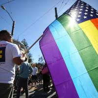 Photo - Larry Pascua carries a rainbow flag at a celebration for the U. S. Supreme Court's rulings on Prop. 8 and the Defense of Marriage Act in the Castro District in San Francisco, on Wednesday, June 26, 2013.  In a major victory for gay rights, the Supreme Court on Wednesday struck down a provision of a federal law denying federal benefits to married gay couples and cleared the way for the resumption of same-sex marriage in California. (AP Photo/Mathew Sumner) ORG XMIT: CAME107