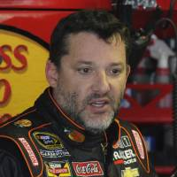 Photo - In this April 11, 2014, photo, Tony Stewart stands in the garage during practice for a NASCAR Sprint Cup series auto race at Darlington Speedway in Darlington, S.C. Authorities are investigating a serious crash that injured one person Saturday, Aug. 9, 2014, at a New York dirt track where Stewart was racing on the eve of a NASCAR race. (AP Photo/Mike McCarn)