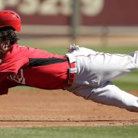 Photo - Cincinnati Reds' Emmanuel Burriss slides into second as he is caught stealing during the third inning of an exhibition spring training baseball game against the Kansas City Royals, Friday, March 1, 2013, in Surprise, Ariz. (AP Photo/Charlie Riedel)