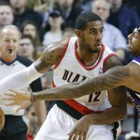 Photo - Portland Trail Blazers forward LaMarcus Aldridge, left, works the ball in against Sacramento Kings forward James Johnson during the first quarter of an NBA basketball game in Portland, Ore., Wednesday, Dec. 26, 2012. (AP Photo/Don Ryan)