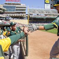 Photo - Oakland Athletics left fielder Sam Fuld, right, is congratulated after hitting a home run against the Minnesota Twins in the fourth inning of a baseball game on Thursday, April 10, 2014 in Minneapolis.(AP Photo/Andy Clayton-King)