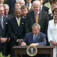 Photo - FILE - This July 27, 2006 file photo shows President George W. Bush signing legislation for a 25 year extension of the Voting Rights Act on the South Lawn of the White House in Washington. The Obama administration and civil rights groups are defending a key provision of the landmark Voting Rights Act at the Supreme Court by pointing reformed state, county and local governments to an escape hatch from the law's most onerous aspects. Wednesday, Feb. 27, 2013, the Supreme Court will hear arguments in the case, which is among the term's most important. From left are Sen. Arlen Specter, R-Pa., Rep. John Conyers, D-Mich., Rep. James Sensenbrenner, R-Wis., and Rep. Nancy Pelosi, D-Calif. (AP Photo/Ron Edmonds, File)