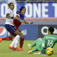 Photo - United States forward Sydney Leroux, center, scores past France goalkeeper Sarah Bouhaddi (16) and defender Laura Georges (4) during the first half of a women's friendly soccer match on Saturday, June 14, 2014, in Tampa, Fla. (AP Photo/Chris O'Meara)