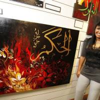 Photo - Artist Farzana Jahangir poses with her painting, which is part of a display at the Midwest City Library. The display includes works by students of Mercy School, a Muslim school in Oklahoma City. PHOTO BY STEVE GOOCH, THE OKLAHOMAN  Steve Gooch - The Oklahoman