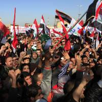 Photo - Protesters chant slogans against Iraq's Shiite-led government as they wave national flags during a demonstration in Baghdad, Iraq, Friday, Jan. 11, 2013. Thousands of protesters took to the street in western Anbar province and other predominantly Sunni areas in Iraq to protest what they believe to be the second-class treatment of Sunnis by the Shiite-led government. (AP Photo/Karim Kadim)