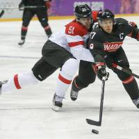 Photo - Canada forward Sidney Crosby gets tangled up with Latvia forward Koba Jass in the first period of a men's ice hockey game at the 2014 Winter Olympics, Friday, Feb. 14, 2014, in Sochi, Russia. (AP Photo/Mark Humphrey)