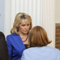 Photo - Gov. Mary Fallin huddles with her staff Thursday before talking with reporters on how the U.S. Supreme Court's decision to uphold the federal health care law will affect Oklahoma. By Paul B. Southerland, The Oklahoma