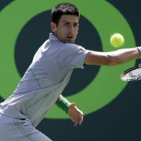 Photo - Novak Djokovic, of Serbia, returns to Tommy Robredo, of Spain, at the Sony Open Tennis tournament, Tuesday, March 25, 2014, in Key Biscayne, Fla. (AP Photo/Lynne Sladky)