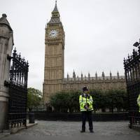 Photo - British police officers stand guard outside the Houses of Parliament in London, Monday, Sept. 1, 2014.  Britain's Prime Minister David Cameron is expected on Monday to expand powers to combat terrorism in hopes of preventing attacks by Islamist militants returning from terror training in the Middle East.  (AP Photo/Matt Dunham)
