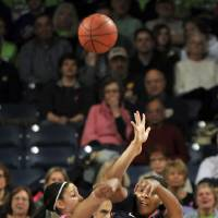 Photo - Syracuse center Shakeya Leary, right, passes as Notre Dame forward Natalie Achonwa defends during first-half action of an NCAA college basketball game on Sunday, Feb. 9, 2014, in South Bend, Ind. (AP Photo/Joe Raymond)