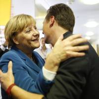 Photo - German Chancellor Angela Merkel, chairwoman of the Christian Democratic party, CDU, greets a supporter at the party headquarters after the national elections  in Berlin Sunday, Sept. 22, 2013.  Chancellor Angela Merkel's conservatives triumphed in Germany's election Sunday, and could even win the first single party majority in more than 50 years. Her center-right coalition partners risked ejection from parliament for the first time in their post-World War II history.(AP Photo/Markus Schreiber)